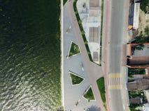 Vista superiore aerea dell'argine della città, strada, lago, parco del pattino Due ragazze stanno trovando su un prato inglese ve fotografie stock libere da diritti