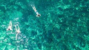 Vista superiore aerea della famiglia che si immerge da sopra, della madre e degli snorkelers dei bambini che nuotano in una chiar fotografia stock libera da diritti