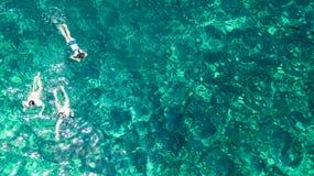 Vista superiore aerea della famiglia che si immerge da sopra, della madre e degli snorkelers dei bambini che nuotano in una chiar fotografie stock libere da diritti