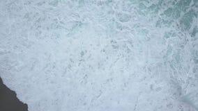 Vista superiore aerea delle onde del mare che spumano e che spruzzano da sopra la rottura sulla spiaggia vuota dell'oceano video d archivio