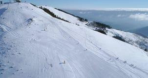 Vista superiore aerea di andata sopra il campo nevoso della pista dello sci della montagna di inverno con la gente nel giorno sol video d archivio