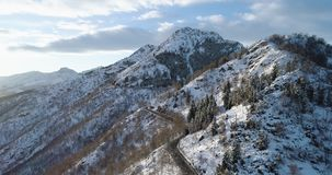 Vista superiore aerea di andata sopra l'automobile che viaggia sulla strada in montagna della neve di inverno vicino al legno del archivi video