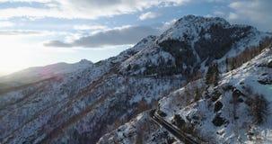 Vista superiore aerea di andata sopra l'automobile che viaggia sulla strada in montagna della neve di inverno vicino al legno del stock footage