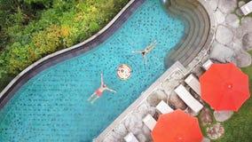 Vista superiore aerea: I giovani si accoppiano con la prima colazione di galleggiamento nella piscina L'uomo e la donna nuotano v immagine stock libera da diritti