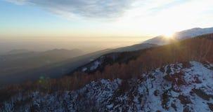 Vista superiore aerea a rovescio sopra la montagna di inverno e la foresta nevose di legni al tramonto o all'alba Sole di penombr stock footage