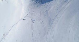 Vista superiore aerea sopraelevata sopra il campo nevoso della pista dello sci della montagna di inverno con la gente nel giorno  archivi video