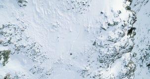 Vista superiore aerea sopraelevata sopra la montagna nevosa di inverno con la gente dello sciatore di alpinismo che cammina sulla archivi video