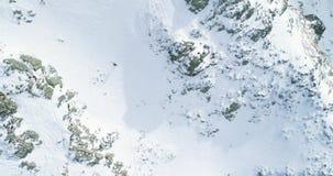 Vista superiore aerea sopraelevata sopra la montagna nevosa di inverno con la gente dello sciatore di alpinismo che cammina sulla stock footage
