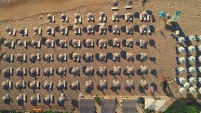 Vista superiore aerea sulla spiaggia Ombrelli, sabbia, sedie del sole ed onde del mare video d archivio