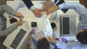 Vista superiore alle mani della gente di affari che si siede alla tavola in ufficio d'avanguardia e che lavora allo sviluppo di a stock footage