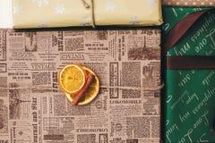 Vista superiore avvolta alla moda dei contenitori di regalo, con il cinna dell'arancia degli ornamenti Immagini Stock