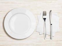 Vista superiore bianca del piatto, del coltello, della forcella e del tovagliolo Immagini Stock