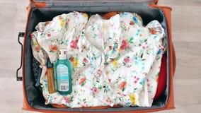 Vista superiore che imballa rapidamente le ragazze della valigia che progettano viaggio Fermata-moto di lasso di tempo video d archivio