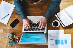 Vista superiore che lavora allo scrittorio con il computer portatile Immagini Stock Libere da Diritti