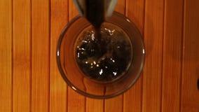 Vista superiore che versa caffè fresco in tazza di caffè di vetro stock footage