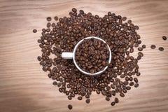 VISTA SUPERIORE: Chicchi di caffè in una tazza bianca e sulla tavola Fotografia Stock