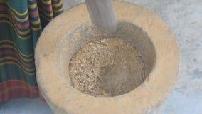 Vista superiore degli ingredienti indiani irriconoscibili della macinazione dell'uomo in un mortaio ed in un pestello di pietra p