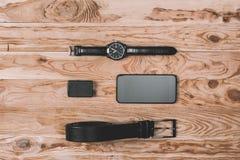 Vista superiore degli orologi dello smartphone, della cinghia, dell'accendino e della mano Fotografia Stock Libera da Diritti
