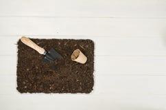 Vista superiore degli strumenti di giardinaggio sul fondo di legno bianco delle plance Fotografia Stock Libera da Diritti