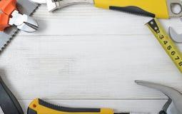 Vista superiore degli strumenti e degli strumenti della costruzione sul banco da lavoro di legno di DIY con spazio aperto Immagine Stock