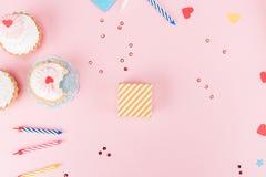 Vista superiore dei bigné deliziosi, delle candele variopinte e dei simboli dei cuori sul rosa Fotografie Stock Libere da Diritti