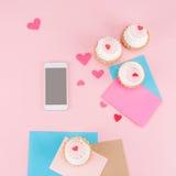 Vista superiore dei bigné deliziosi, dello smartphone con lo schermo in bianco e dei simboli dei cuori sul rosa Fotografie Stock Libere da Diritti