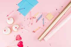 Vista superiore dei bigné, delle candele variopinte e della carta da imballaggio sul rosa Immagini Stock Libere da Diritti