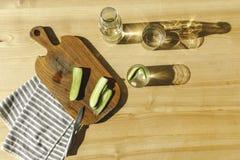 vista superiore dei cetrioli tagliati e dell'acqua antiossidante su di legno immagine stock libera da diritti