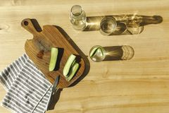 vista superiore dei cetrioli tagliati e dell'acqua antiossidante su di legno fotografia stock