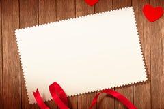 Vista superiore dei cuori e del nastro rossi decorativi con la cartolina d'auguri su vecchio fondo di legno, concetto del giorno  Fotografie Stock
