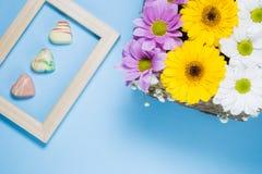 Vista superiore dei cuori floreali della pralina del belga e della decorazione incorniciati su fondo blu fotografia stock