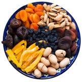 Vista superiore dei frutti secchi centroasiatici e dei dadi in un piatto ceramico blu tipico isolato su fondo bianco secco Fotografia Stock Libera da Diritti
