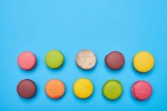 Vista superiore dei macarons dolci con lo spazio della copia sopra flatlay blu Fotografia Stock