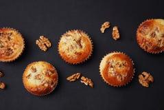 Vista superiore dei muffin casalinghi con i dadi su fondo nero in uno stile rustico Selezioni il punto del fuoco Fotografie Stock
