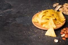 Vista superiore dei nacho gialli luminosi su un piatto rotondo di legno leggero Chip di cereale con i dadi misti su un fondo nero immagini stock libere da diritti