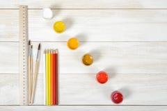Vista superiore dei pennelli e delle matite con i contenitori variopinti di gouache su fondo di legno Immagini Stock