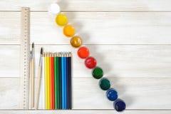 Vista superiore dei pennelli e delle matite con i contenitori variopinti di gouache su fondo di legno Fotografie Stock Libere da Diritti