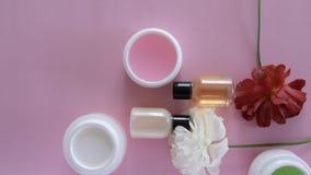 Vista superiore dei prodotti differenti e fiori igienici/cosmetici su fondo rosa fresco Trattamento di bellezza di benessere archivi video