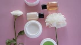 Vista superiore dei prodotti differenti e fiori igienici/cosmetici su fondo rosa fresco Trattamento di bellezza di benessere stock footage