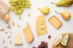 Vista superiore dei tipi differenti di formaggio, di uva, di pere, di mandorla e di baguette su bianco fotografie stock libere da diritti