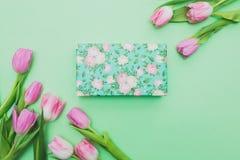 Vista superiore dei tulipani e del contenitore di regalo rosa su fondo verde chiaro con lo spazio della copia Immagine Stock