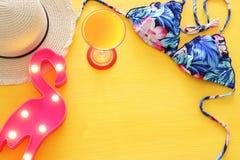 Vista superiore del bikini e del cappello femminili del costume da bagno di modo sopra fondo di legno giallo Concetto di vacanza  fotografia stock