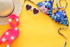 Vista superiore del bikini e del cappello femminili del costume da bagno di modo sopra fondo di legno giallo Concetto di vacanza  immagine stock