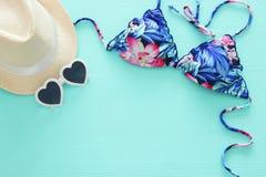 Vista superiore del bikini femminile del costume da bagno di modo e del cappello bianco della fedora sopra il fondo di legno dell fotografia stock