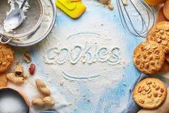 Vista superiore del biscotto di parola scritta sull'insieme di prodotto e della farina per la cottura dei biscotti Fotografie Stock