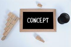Vista superiore del CONCETTO scritta a mano con gesso bianco su una lavagna Tazza della matita e blocco di legno che impilano com immagini stock