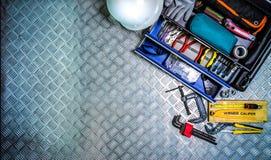 Vista superiore del contenitore e del casco di strumenti sul fondo a quadretti del piatto in officina Assista l'insieme di strume Fotografia Stock Libera da Diritti