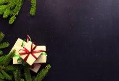 Vista superiore del fondo scuro tradizionale di Natale Regali del ` s del nuovo anno con il ramo rosso e verde dell'abete rosso d immagine stock