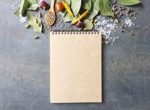 Vista superiore del libro di cucina in bianco e lotto degli spieces e delle erbe sul tavolo da cucina grigio Spazio vuoto per il  fotografie stock