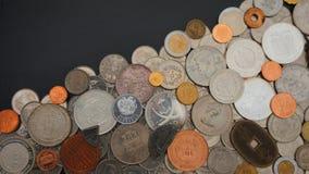 Vista superiore del lotto delle monete dei paesi differenti del mondo disordinato sulla tavola nera Immagine Stock